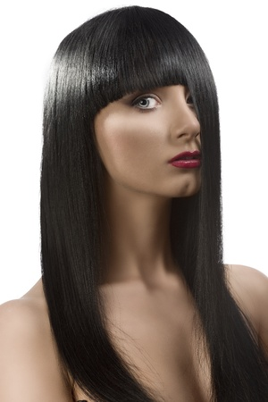 pretty girl with long, dark smooth hair and fringe, she is turned of three quarters at left with the left side of the face hidden by the hair, she looks in to the lens photo