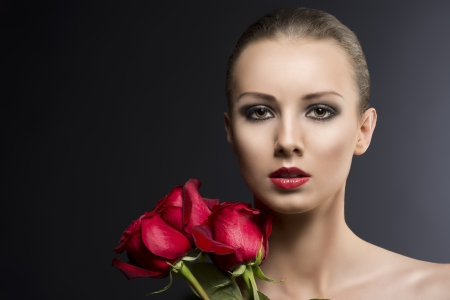 pretty blonde girls low key portrait with three red roses, she is in front the camera and looks in to the lens photo