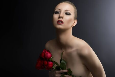 pretty blonde girls low key portrait with three red roses, she is turned at three quarters at right, looks in to the lens with sensual expression and takes the roses near the chest photo