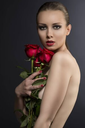 pretty blonde girls low key portrait with three red roses, her body is turned in profile,  looks in to the lens and she takes the roses near the face photo