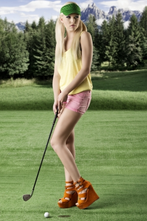 pretty blonde girls playng golf with golf club, pink shorts and green sunshade, her body is turned of three quarters at right and she looks at left  photo