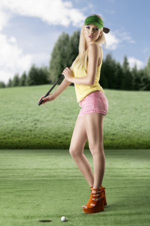 pretty blonde girls playng golf with golf club, pink shorts and green sunshade, she is turned of three quarters at right, looks in to the lens with sexy expression and takes the golf club on her right shoulder photo