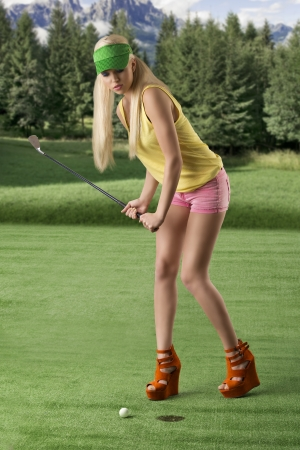 pretty blonde girls playng golf with golf club, pink shorts and green sunshade, she is turned of three quarters at right and she is hitting the golf ball photo