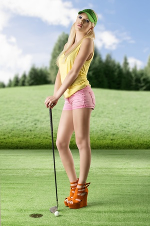 pretty blonde girls playng golf with golf club, pink shorts and green sunshade, she is turned of three quarters at right, looks in to the lens and her hands are on the golf club photo
