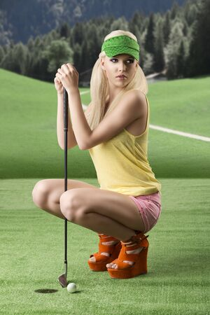 pretty blonde girls playng golf with golf club, pink shorts and green sunshade, she is turned of three quarters at right, folded down with golf club between her legs photo