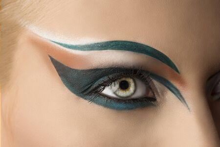 girls eye closeup with creative green makeup. its open photo