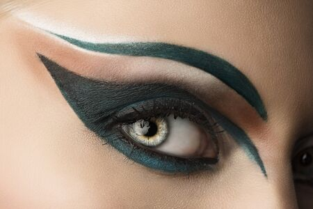 girls eye closeup with creative green makeup, it looks at right photo