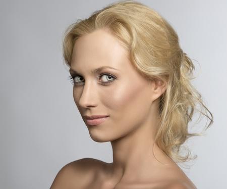 schönes blondes Mädchen mit Akten Schultern und natürliche Make-up, sie von drei Vierteln auf rechts gedreht wird, sieht in der Linse und lächelt