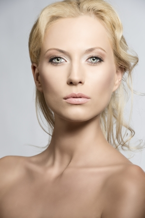 elegance fashion girls look sensuality young: beautiful blonde girl with nudes shoulders and natural makeup, she is in front of the camera and looks in to the lens with sensal expression