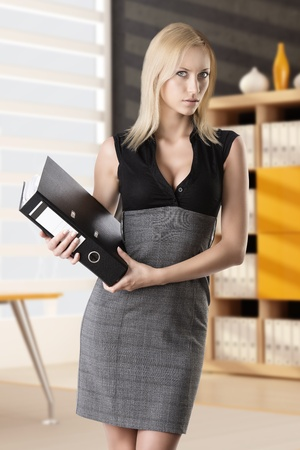 classifier: pretty business woman with elegant dress and classifier, she is in front of the camera, looks in to the lens and takes the classifier with right hand Stock Photo
