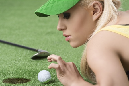 pretty blonde girl is lying on the grass and playing with golf ball, she is in profile and looks the ball photo