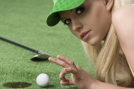pretty blonde girl is lying on the grass and playing with golf ball, she is turned of three quarters and looks in to the lens, she is about to hits the ball with left hand