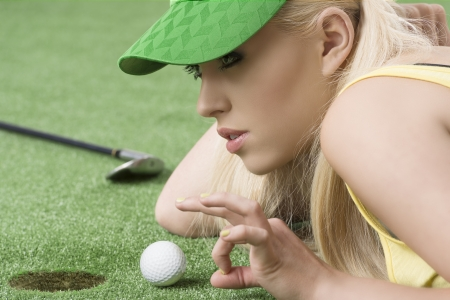 pretty blonde girl is lying on the grass and playing with golf ball, she is about to hits the ball with left hand photo
