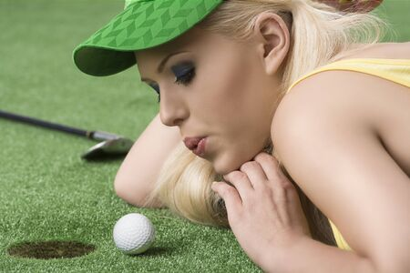 woman golf: pretty blonde girl is lying on the grass and playing with golf ball, she is in profile, looks the ball and blows on that