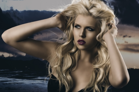 portrait of young sexy girl with blode wavy hairstyle and and flying hair from wind, she is turned of three quarters at right and her hands are on the head in the hair Stock Photo - 14705045