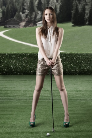sexy woman in glitter shorts and hig shoes plays golf, she is in front of the camera, looks in to the lens and takes the golf-club with both hands photo