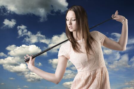 sportive: pretty girl with pink elegant dress and golf-club, she looks down at right and takes the golf-club on the shoulders Stock Photo