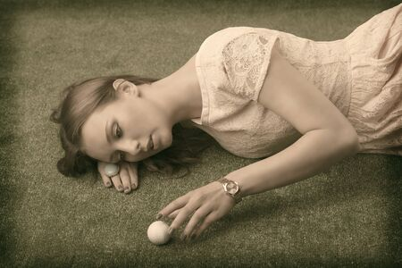 vintage shot of Pretty girl with brown hair lying on grass and playing with golf ball, she looks the ball and touches that photo