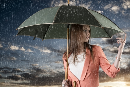 rain coat: pretty young woman with green umbrella, under summer rain during a beautiful sunset