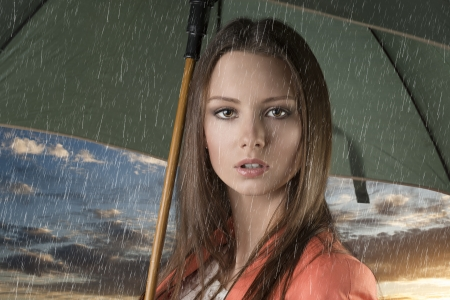 pretty young woman with green umbrella,close up under summer rain on sunset photo