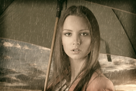 sotto la pioggia: ritratto d'epoca di bella giovane donna con ombrello verde, close up sotto la pioggia d'estate sul tramonto