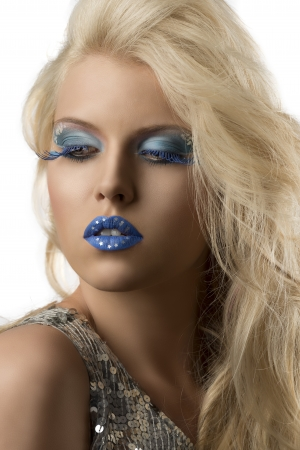 sexy blonde girl with blue creative make-up and glitter dress, she is slighlty turned of three quarters and looks down at right photo