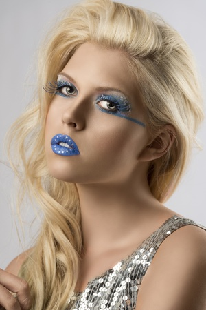 sexy blonde girl with euro flag make-up and glitter dress, she is turned of three quarters and looks in to the lens photo
