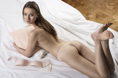 Sexy girl from behind lying on the bed with her bra placed next, she takes the pillow in her arms and looks in to the lens Stock Photo