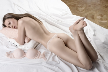 Sexy girl from behind lying on the bed with her bra placed next, she has her head on the pillow and looks at left Stock Photo