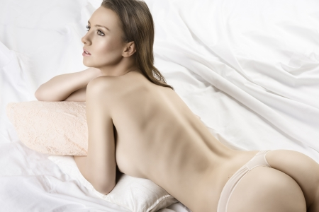 Sexy girl from behind lying on the bed, she has the right hand near the neck and looks at left