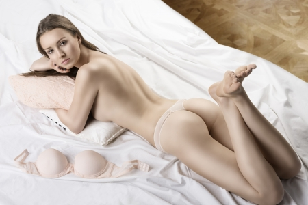 Sexy girl from behind lying on the bed with her bra placed next, her foots are crossed, she looks in to the lens with face on the right hand
