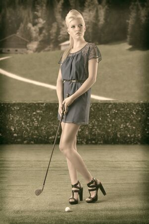 beautiful blonde girl in full lenght plays golf with blue short dress and hig shoes, vintage color shot photo