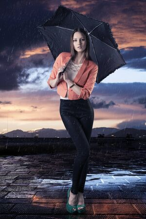 pretty young woman with dark umbrella, she is in front of the camera and looks in to the lens photo
