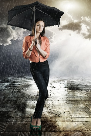 pretty young woman with dark umbrella, she is in front of the camera, looks in to the lens and takes the umbrella with both hands photo