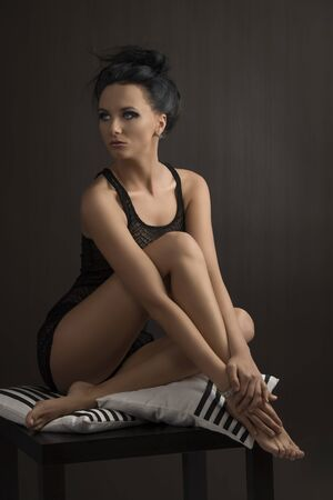 pretty brunette is sitting on pillows with tied back hair, she looks at right with right leg between her arms photo