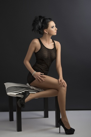pretty brunette is sitting on pillows with tied back hair, her face is turned in profile at left and her hands are on legs photo