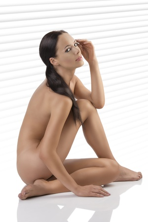 naked girl body: pretty brunette is naked and sitting on a floor, she is turned in profile at left, looks in to the lens and has the left hand near the eye