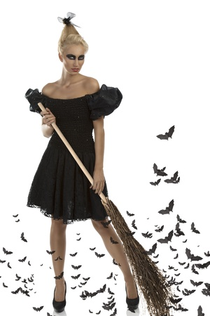 sibyl: pretty blonde girl with gothic dress, dark make-up and besom, she takes the besom with both hands and looks in to the lens