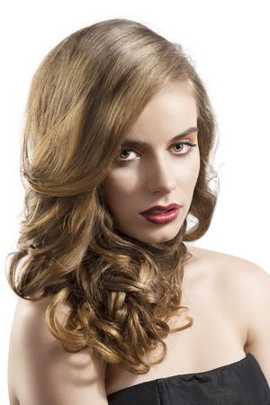 pretty girl with wavy hair and red lipstick, she is turned of three quarters at left looks in to the lens with hair on the right shoulder Stock Photo - 15785121