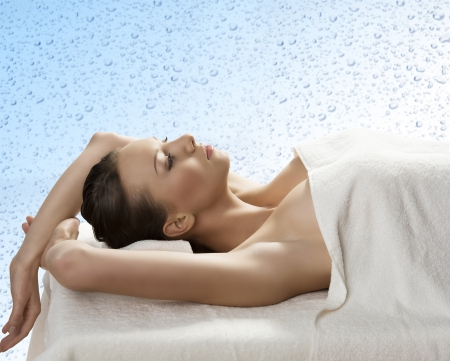 beautiful girl lying on a table with withe towel on her body and under her head, she is in profile with both arms raised behind the head Stock Photo