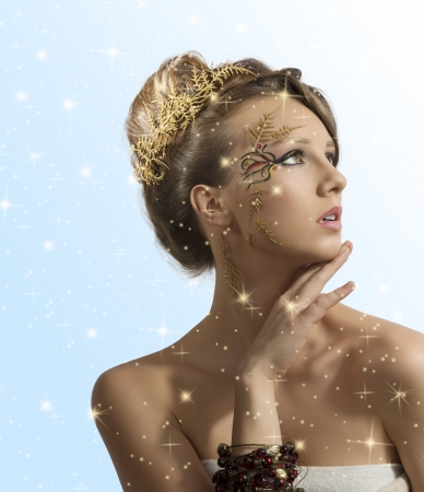 beautiful woman with christmas make-up and hair decoration, she looks at left with hand under the chin photo