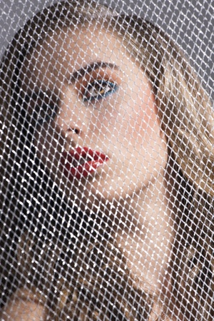 pretty girl with coloured make-up behind grid, she is turned of three quarters at right Stock Photo - 16016409
