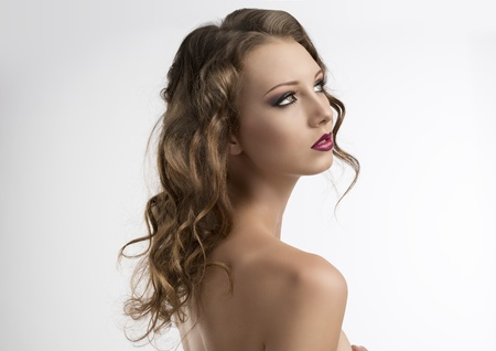 pretty girl with long wavy hair and purple make-up, she is turned of three quarters at left and looks up in front of her Stock Photo - 16143460