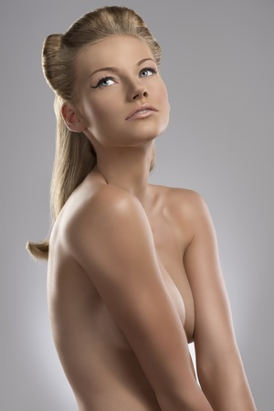 pretty blonde girl with nude torso and creative hair style, she is turned of three quarters at left and looks up photo