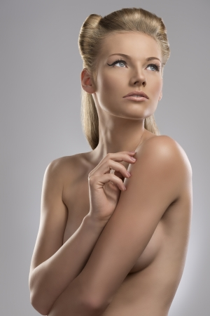 pretty blonde girl with nude torso and creative hair style, she is turned of three quarters at right and looks up at left photo