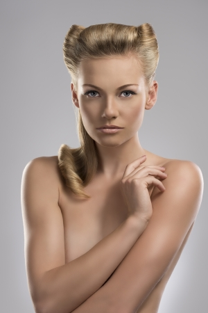 pretty blonde girl with nude torso and creative hair style, she looks in to the lens and her right hand is near the left shoulder photo