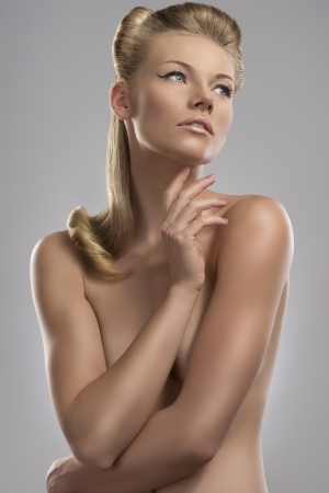 pretty blonde girl with nude torso and creative hair style, she looks at left and her right hand is near the chin  photo