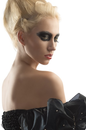beautiful vampire: pretty blonde girl with creative dark make-up and upward hairstyle, she is turned at left, looks down and shows her nacked right shoulder