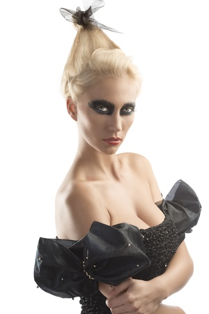 gothic woman: pretty blonde girl with creative dark make-up and upward hairstyle, she is turned of three quarters at left and she touches her right elbow with left hand
