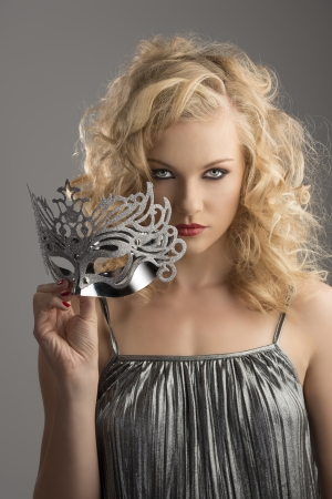 silver dress: pretty blonde girl with curly hair takes one silver mask, she takes the mask with right hand and looks in to the lens